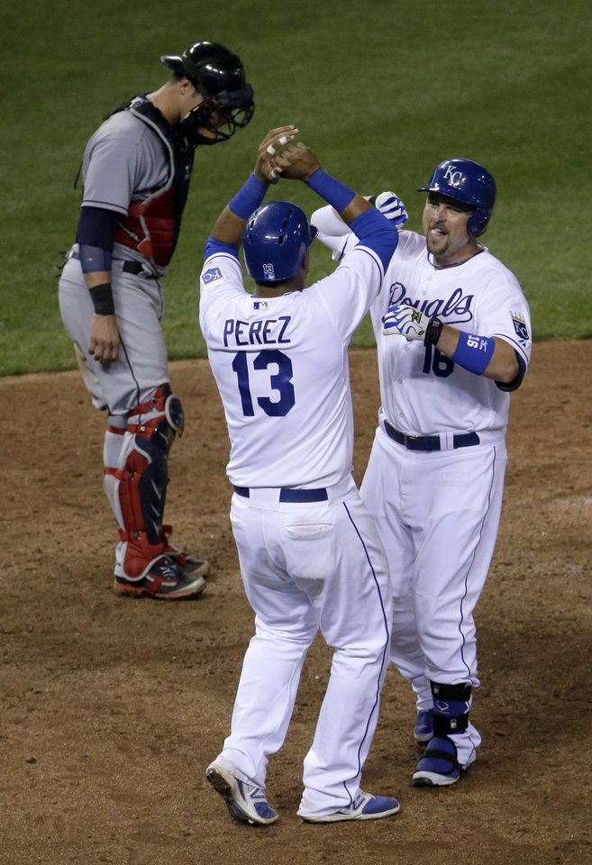 Photo - Kansas City Royals' Billy Butler (16) celebrates with Salvador Perez after hitting a two-run home run during the eighth inning of a baseball game against the Cleveland Indians, Friday, July 25, 2014, in Kansas City, Mo. (AP Photo/Charlie Riedel)