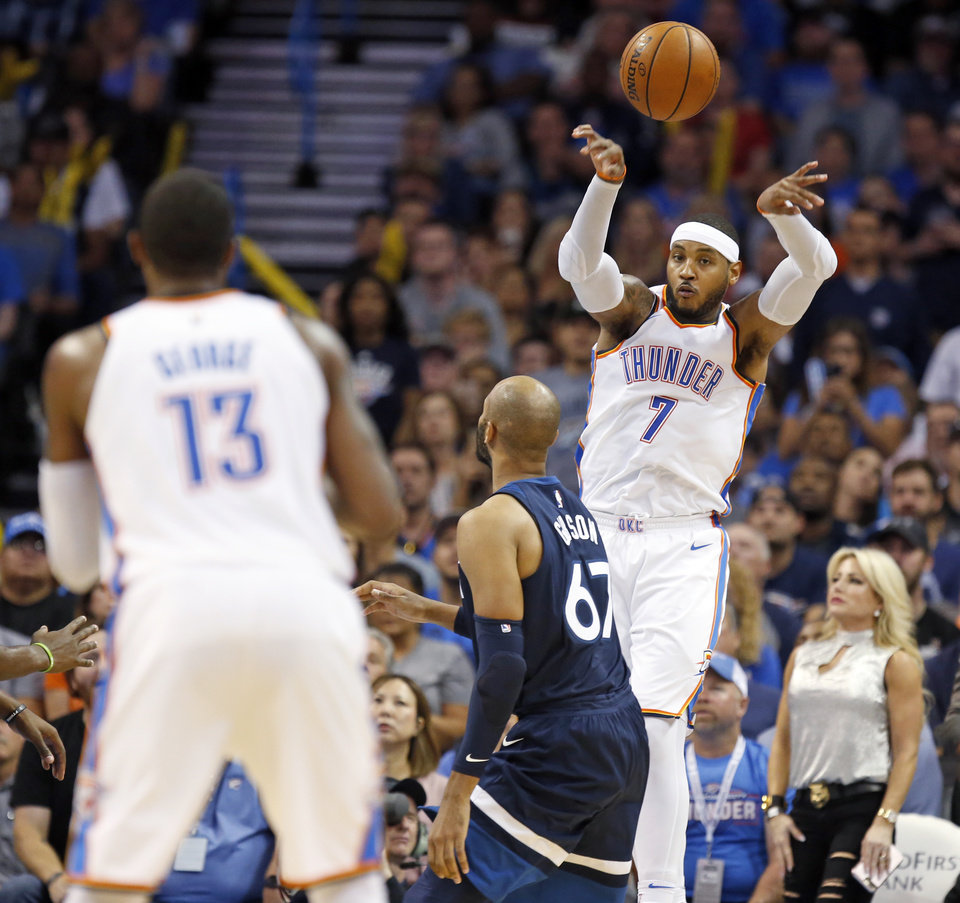 Photo - Oklahoma City's Carmelo Anthony (7) passes over Minnesota's Taj Gibson (67) to Paul George (13) during an NBA basketball game between the Oklahoma City Thunder and the Minnesota Timberwolves at Chesapeake Energy Arena in Oklahoma City, Sunday, Oct. 22, 2017. Minnesota won 115-113. Photo by Nate Billings, The Oklahoman