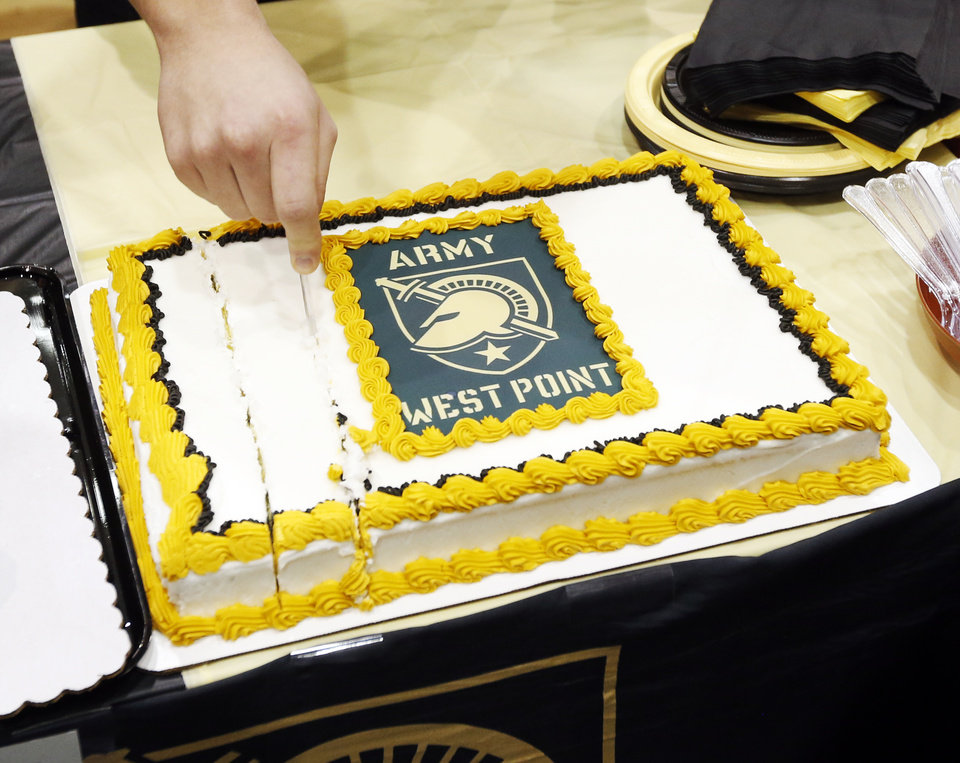 Photo - Hunter Richard cuts a cake after he signed to attend Army West Point where he will play football, during a ceremony for National Signing Day at Edmond North High School in Edmond, Okla., Wednesday, Feb. 7, 2018. Photo by Nate Billings, The Oklahoman