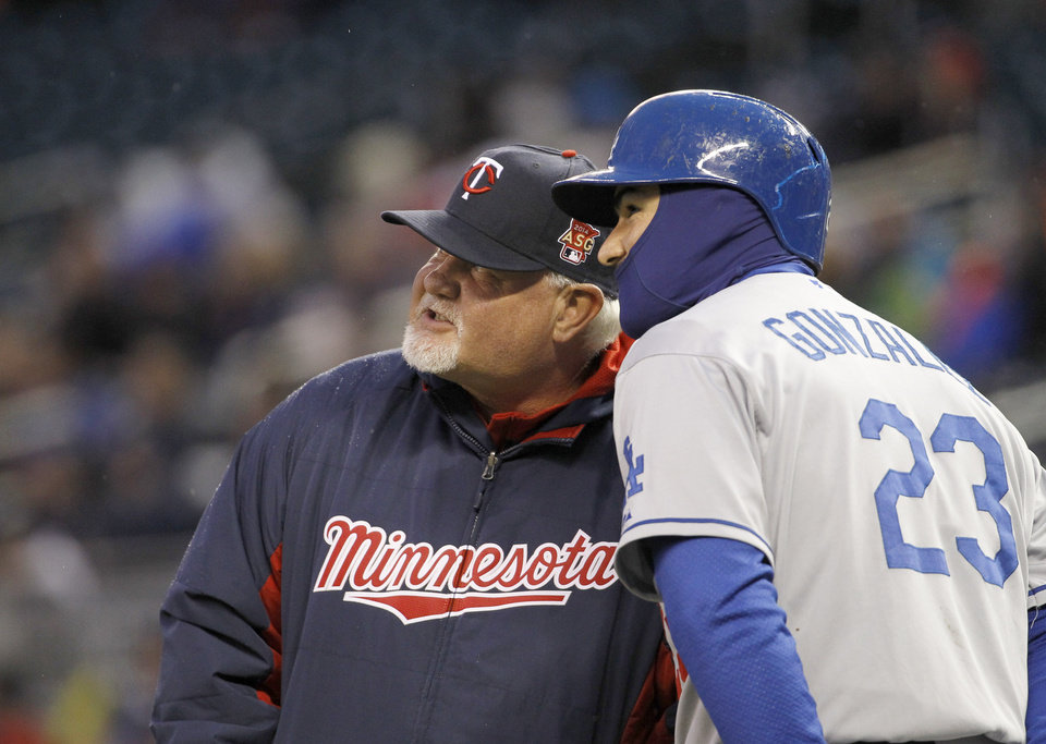 Photo - Minnesota Twins manager Ron Gardenhire, left, and Los Angeles Dodgers' Adrian Gonzalez (23) watch a replay of a play at home plate after Gardenhire requested a review during the third inning of a baseball game in Minneapolis, Wednesday, April 30, 2014. The initial call stood and Drew Butera was ruled safe at home plate. (AP Photo/Ann Heisenfelt)