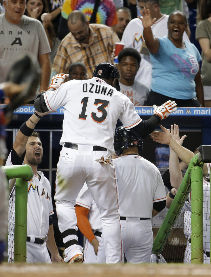 Photo - Miami Marlins' Marcell Ozuna (13) is met in the dugout after hitting a solo home run in the fourth inning during a baseball game against the Texas Rangers, Tuesday, Aug. 19, 2014, in Miami. (AP Photo/Lynne Sladky)