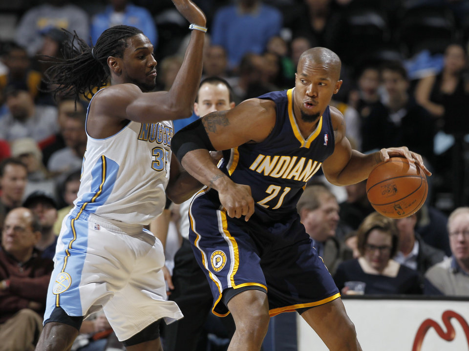 Photo - Indiana Pacers forward David West, right, works the ball inside for a shot as Denver Nuggets forward Kenneth Faried defends in the first quarter of an NBA basketball game in Denver on Monday, Jan. 28, 2013. (AP Photo/David Zalubowski)