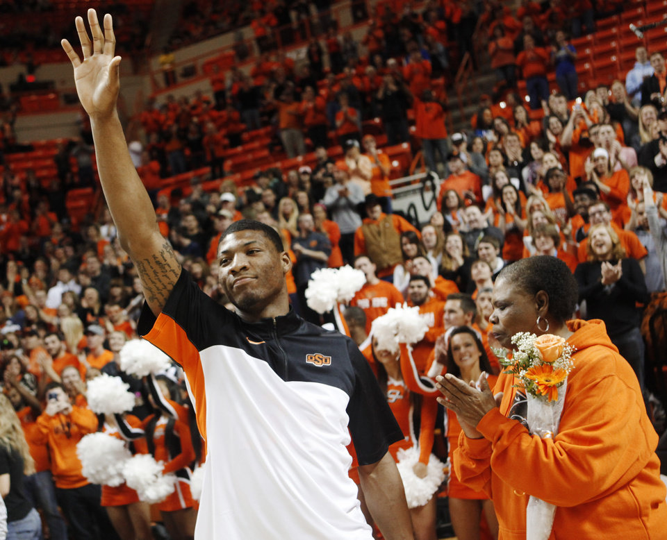 OSU guard Marcus Smart waves to fans as he is introduced during Monday night's matchup against Kansas State.                    Photo by KT King, The Oklahoman