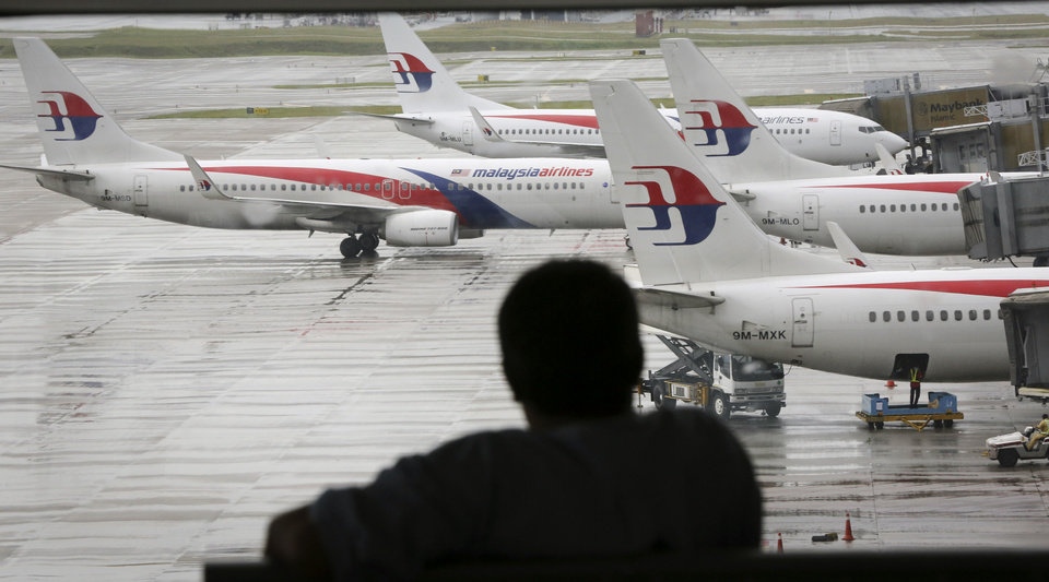 Photo - A visitor looks out from the viewing gallery as Malaysia Airlines aircraft sit on the tarmac at the Kuala Lumpur International Airport (KLIA) in Sepang, Malaysia, Tuesday, May 27, 2014. The Malaysian government on Tuesday released 45 pages of raw satellite data it used to determine the flight path of the missing jetliner, information long sought after by some of the relatives of the 239 people on board the plane. (AP Photo/Vincent Thian)