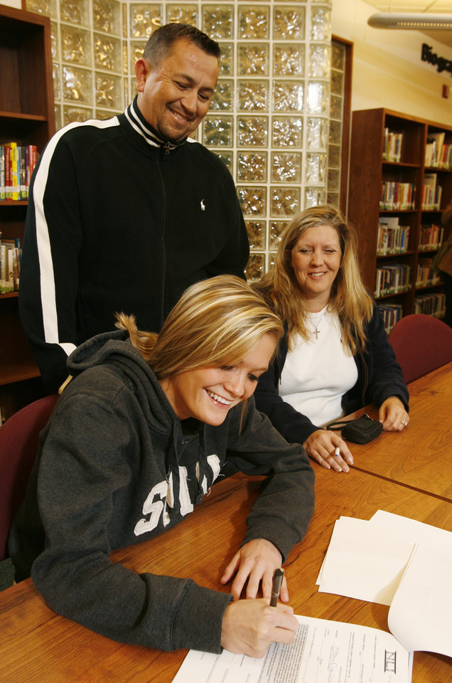Photo - LETTER OF INTENT / PARENT / FAMILY / GIRLS HIGH SCHOOL SOCCER / SIGNING DAY / SIGN: Soccer player Calli Cooper signs a letter of intent to attend SMU as her mother Traci Cooper and step-father/coach James Soesbee watch at Norman North High School in Norman, Okla. on Wednesday, Feb. 4, 2009.    Photo by Steve Sisney, The Oklahoman ORG XMIT: kod