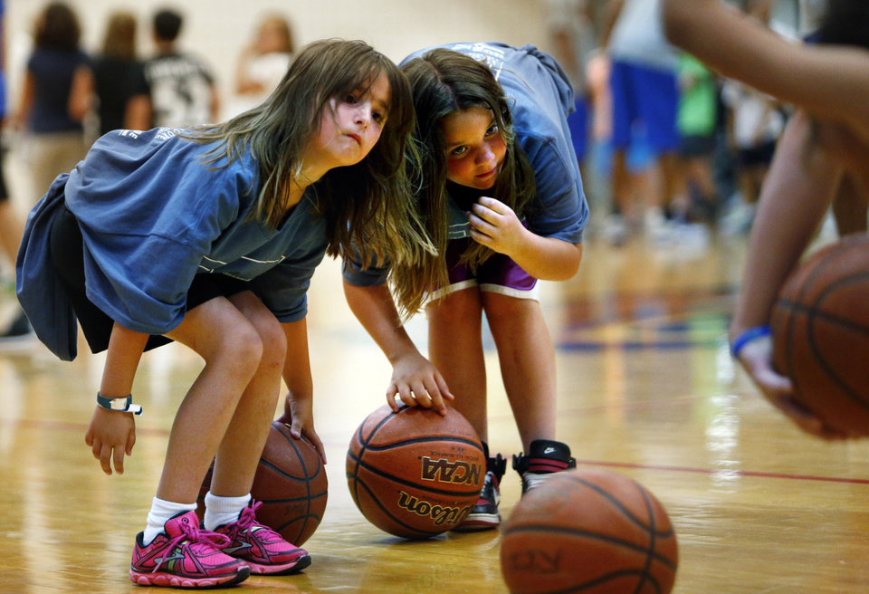 Plaza Towers student Addyson Roberts, 7, and Sky Ranch student Dacelyn Moore, 9, participate in drills as former NBA All-Stars Danny Manning, Otis Birdsong and Michael Ray Richardson host a basketball clinic for tornado victims on Thursday, June 13, 2013 in Moore, Okla.  Photo by Steve Sisney, The Oklahoman