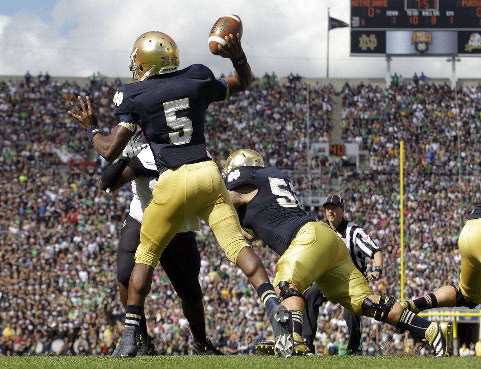 Photo -   FILE - In this Sept. 8, 2012, file photo, Notre Dame quarterback Everett Golson looks to pass as cetner Braxston Cave, right, blocks during during the first half of an NCAA college football game against Purdue in South Bend, Ind. All too often last week the Irish offensive line struggled against Purdue, allowing four sacks and rushing for just 53 yards. The linemen are looking for redemption against No. 10 Michigan State's tough defensive line on Saturday.(AP Photo/Michael Conroy, File)