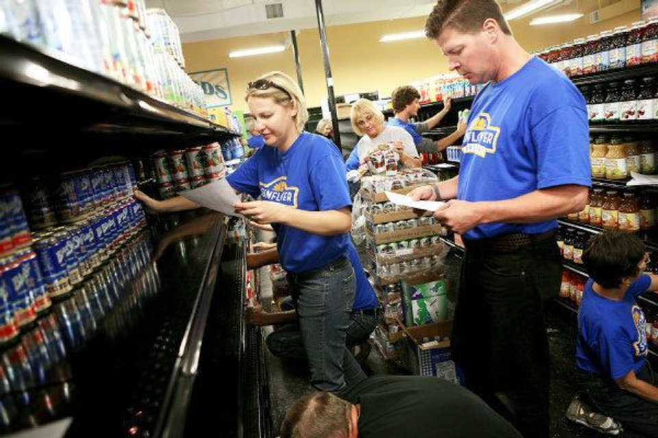 Brandi Brady (left) and Bruce Brunswick work to stock the shelves at the new Sunflower Farmers Market at NW 63 and N May Avenue. JOHN CLANTON - John Clanton