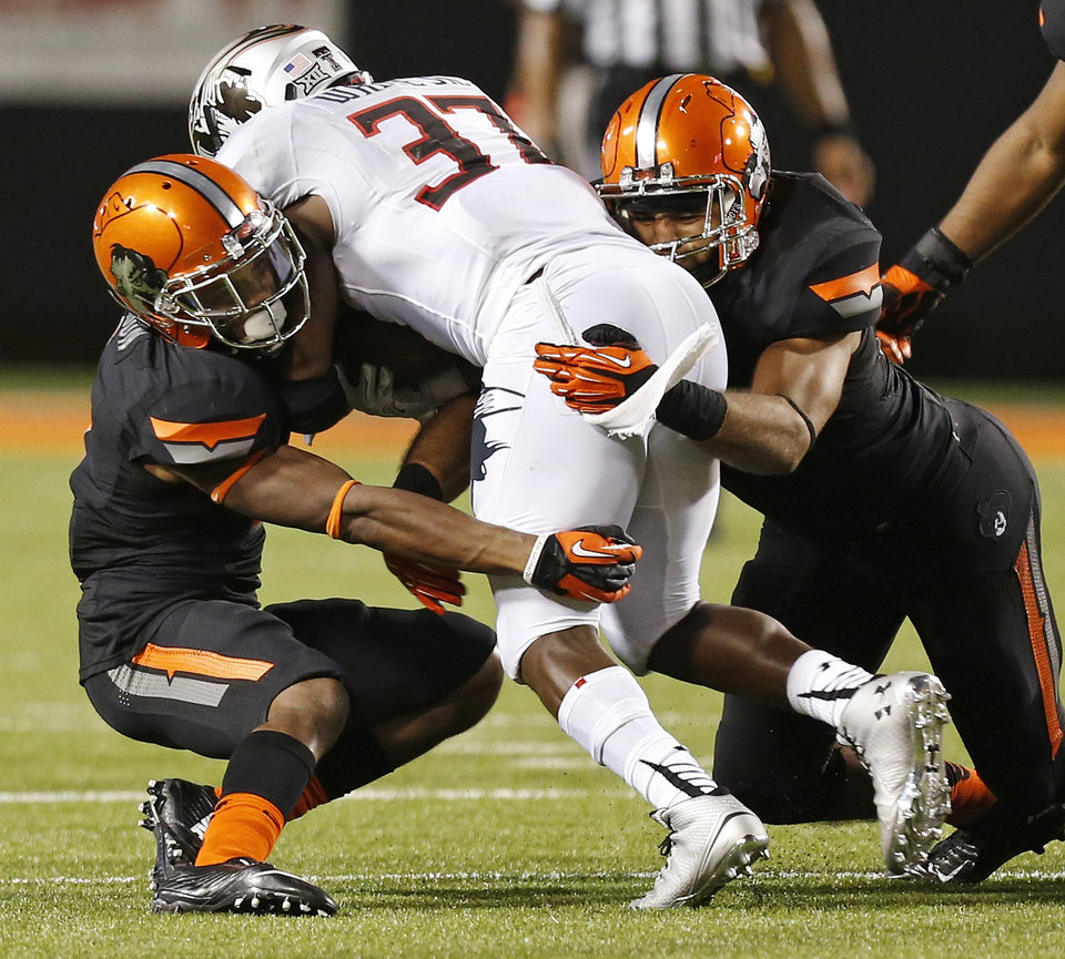 Photo - Oklahoma State's Kevin Peterson (1), left, and Seth Jacobs (10) bring down Texas Tech's Quinton White (37) during a college football game between the Oklahoma State Cowboys (OSU) and the Texas Tech Red Raiders at Boone Pickens Stadium in Stillwater, Okla., Thursday, Sept. 25, 2014. OSU won, 45-35. Photo by Nate Billings, The Oklahoman