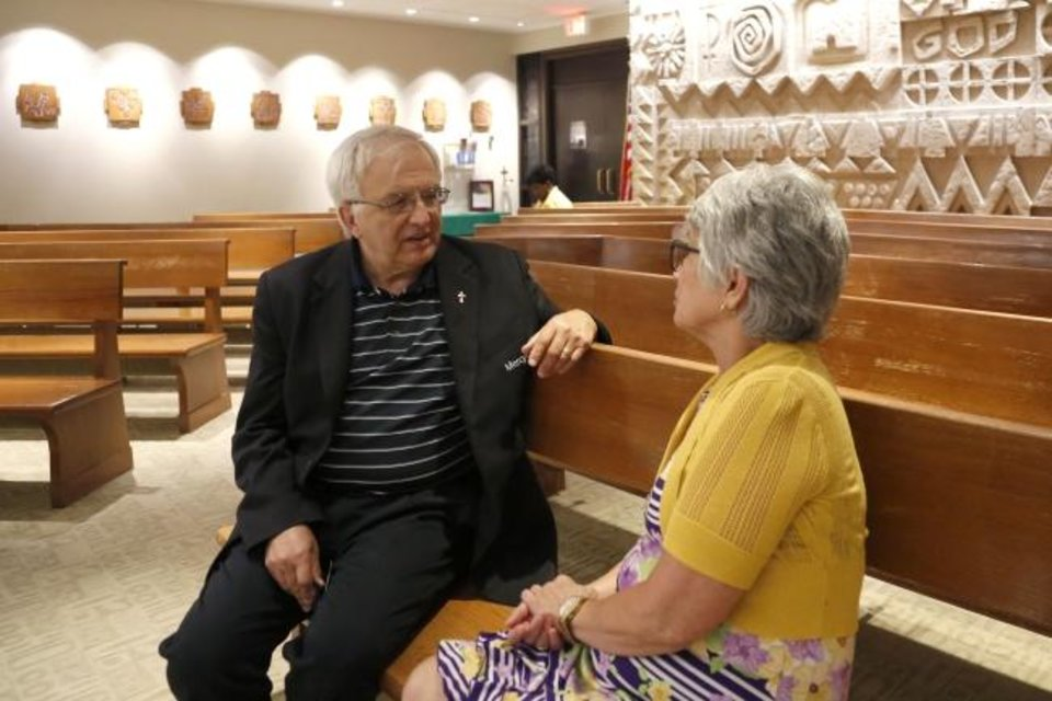 Photo -  Richard Thibodeau, manager of pastoral care at Mercy Hospital, talks with volunteer Pat McClure in the hospital's chapel. [Paxson Haws/The Oklahoman]