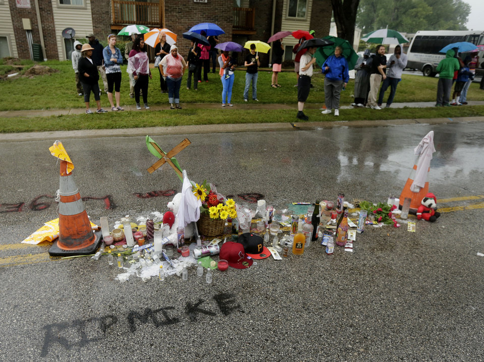 Photo - People gather next to a makeshift memorial for Michael Brown Saturday, Aug. 16, 2014, located at the site where Brown was shot by police a week ago in Ferguson, Mo. Brown's shooting in the middle of a street following a suspected robbery of a box of cigars from a nearby market has sparked a week of protests, riots and looting in the St. Louis suburb. (AP Photo/Charlie Riedel)