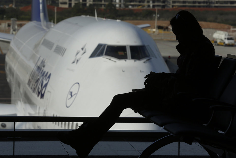 Photo - A passenger reads a book as she waits to board at the Sao Paulo International airport in Guarulhos, Brazil, Tuesday, May 20, 2014. The chronic delays in airport renovations have matched those in stadium construction, and officials have acknowledged for a while that visitors will be using unfinished airport facilities. Brazil is trying to assure World Cup tourists that they won't face problems at airports even though not all upgrades will be complete. (AP Photo/Andre Penner)
