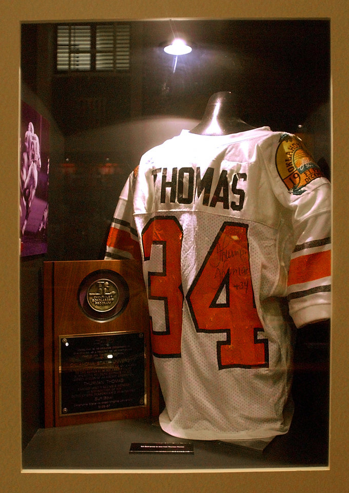 Photo - A signed jersey from OSU's all-time leading rusher Thurman Thomas is on display at OSU's Heritage Hall in Gallagher-Iba Arena on the campus of Oklahoma State University in Stillwater. [Nate Billings/The Oklahoman]