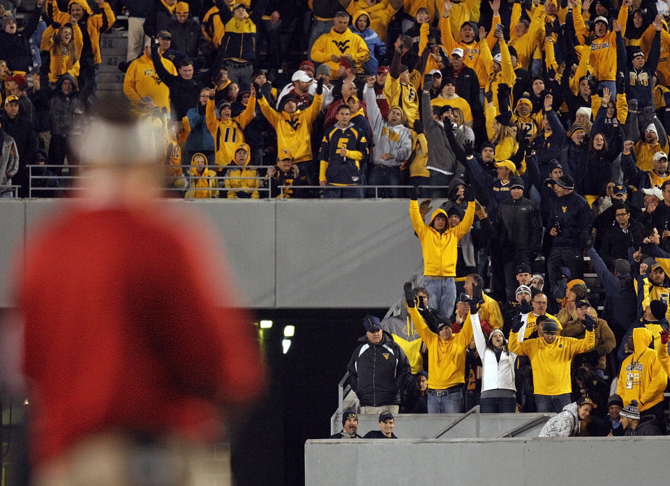 Photo - West Virginia fans react after a Mountaineer touchdown was confirmed by replay as OU head coach Bob Stoops stands on the sideline during a college football game between the University of Oklahoma and West Virginia University on Mountaineer Field at Milan Puskar Stadium in Morgantown, W. Va., Nov. 17, 2012. OU won, 50-49. Photo by Nate Billings, The Oklahoman