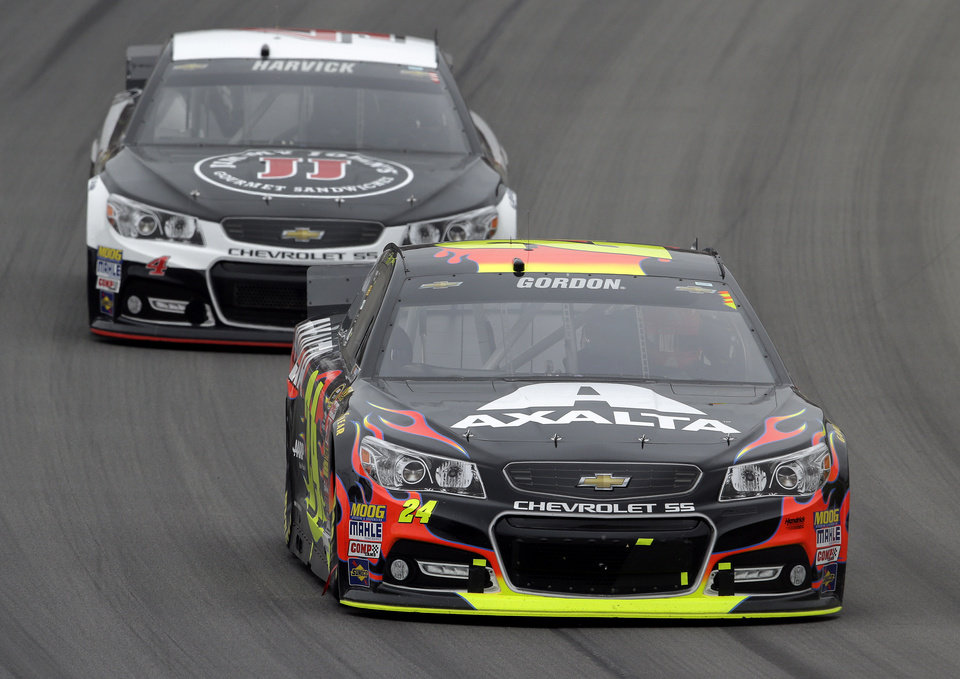 Photo - Jeff Gordon (24) races Kevin Harvick during the NASCAR Sprint Cup Series Pure Michigan 400 auto race at Michigan International Speedway in Brooklyn, Mich., Sunday, Aug. 17, 2014. (AP Photo/Paul Sancya)