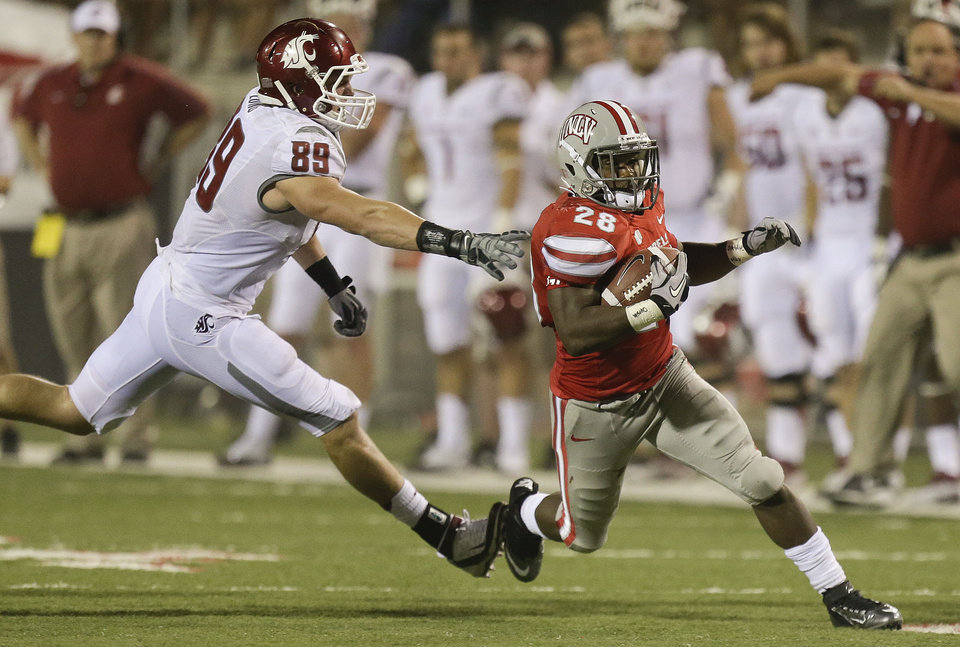 Photo -   UNLV running back Bradley Randle (28) avoids the grasp of Washington State linebacker Travis Long (89) in the fourth quarter during an NCAA college football game, Friday, Sept. 14, 2012, in Las Vegas. (AP Photo/Julie Jacobson)