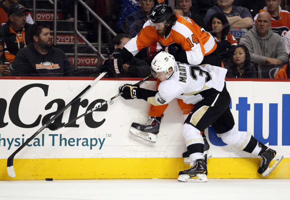 Photo - Philadelphia Flyers' Sean Couturier, top, and Pittsburgh Penguins' Olli Maatta battle for the puck along the boards during the second period of an NHL hockey game, Saturday, March 15, 2014, in Philadelphia. (AP Photo/Tom Mihalek)
