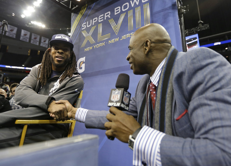 Photo - Deion Sanders shakes hands with Seattle Seahawks' Richard Sherman during media day for the NFL Super Bowl XLVIII football game Tuesday, Jan. 28, 2014, in Newark, N.J. (AP Photo/Jeff Roberson)