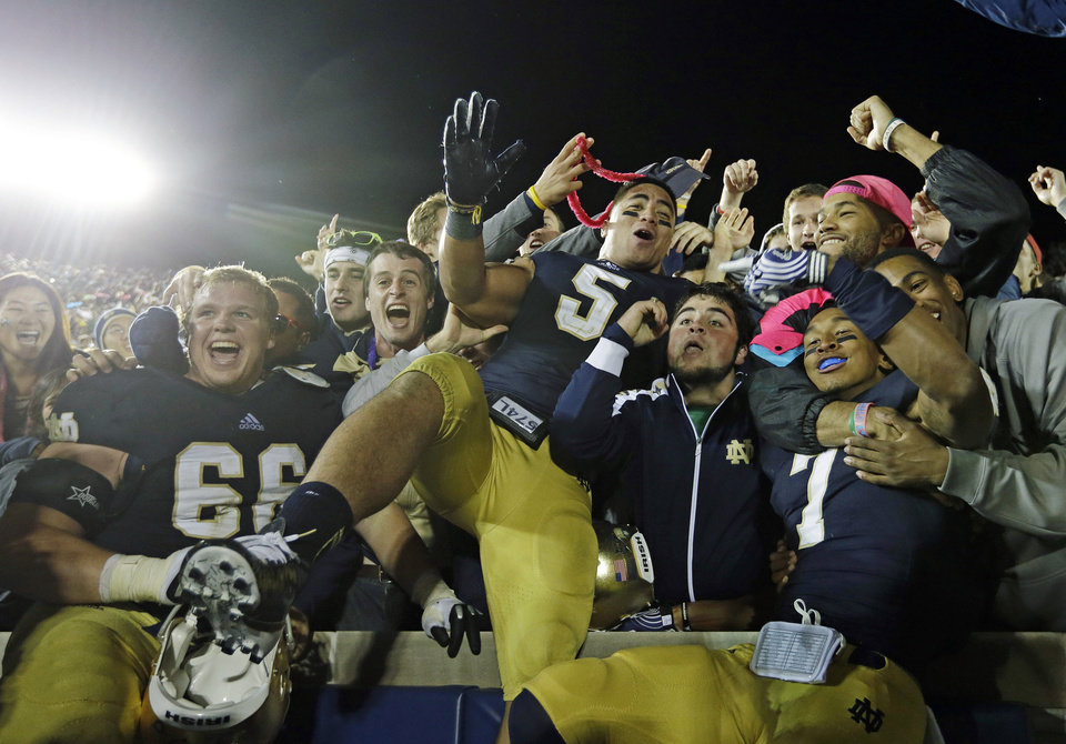 In this Sept. 22, 2012 photo, Notre Dame's Chris Watt (66), Manti Te'o (5) and TJ Jones (7) celebrate with fans after Notre Dame defeated Michigan, 13-6, in an NCAA college football game in South Bend, Ind. Notre Dame defensive coordinator Bob Diaco believes Manti Te�o is the finest football player in college. (AP Photo/Darron Cummings)