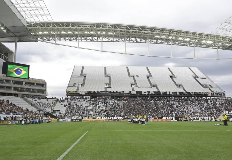 Photo - Corinthians's and Botafogo players listen to the national anthem prior to a Brazilian soccer league match at the Itaquerao, the stadium that will host the World Cup opener match between Brazil and Croatia on June 12, in Sao Paulo, Brazil, Sunday, June 1, 2014. (AP Photo/Andre Penner)