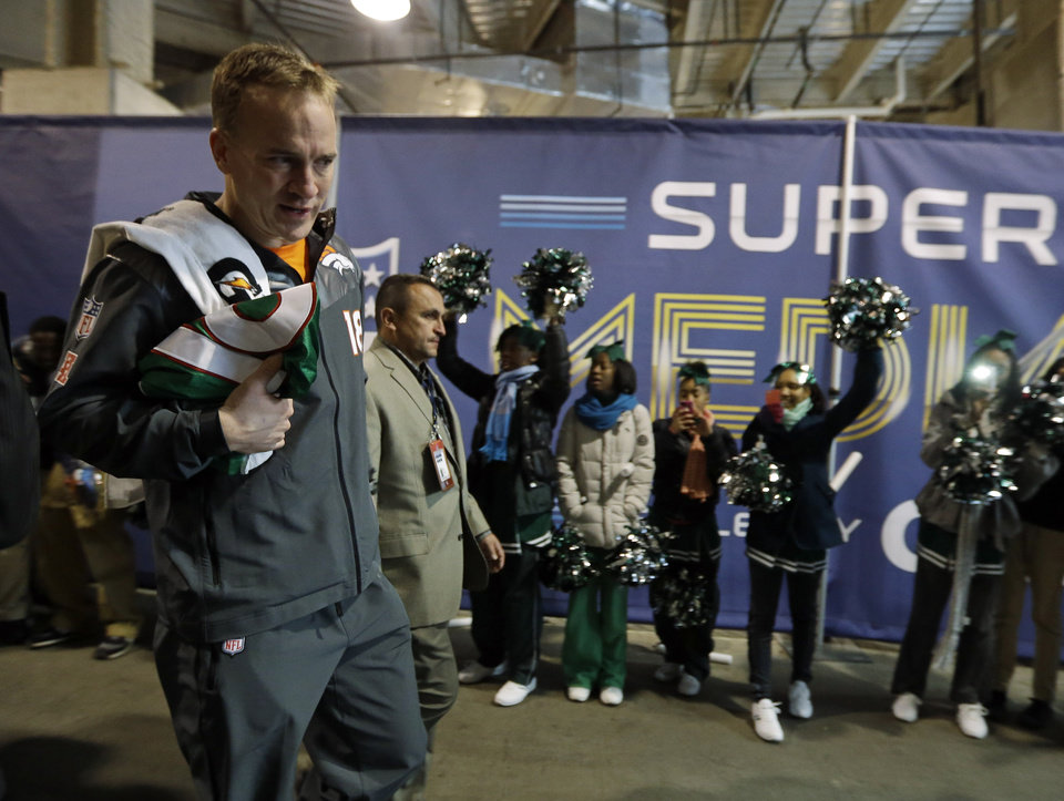 Photo - Denver Broncos' Peyton Manning walks past some cheerleaders as he leaves media day for the NFL Super Bowl XLVIII football game Tuesday, Jan. 28, 2014, in Newark, N.J. (AP Photo/Jeff Roberson)