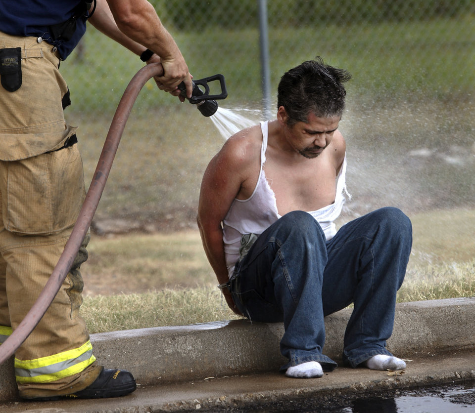 A firefighter sprays water on a handcuffed suspect. City police forced entry into a second floor motel room Saturday afternoon, July 14, 2012, and arrested a man inside the room.  Police were responding to a call reporting a strong odor coming from one one of the rooms  facing the courtyard. When the subject was taken from the room, he was immediately washed down with water by a firefighter. Motel guests were evacuated from their rooms before police swarmed the room.  Photo by Jim Beckel, The Oklahoman.