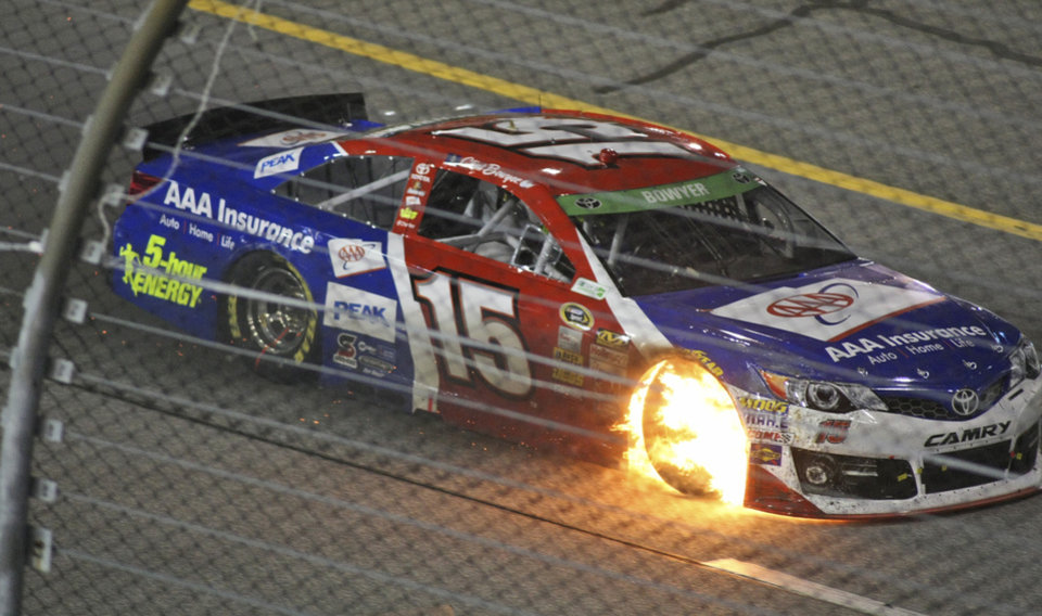 Clint Bowyer (15) heads to the pits with flames coming out of the wheel well during the NASCAR Sprint Cup auto race at Richmond International Raceway in Richmond, Va., Saturday, April 26, 2014. (AP Photo/Jason Hirschfeld)