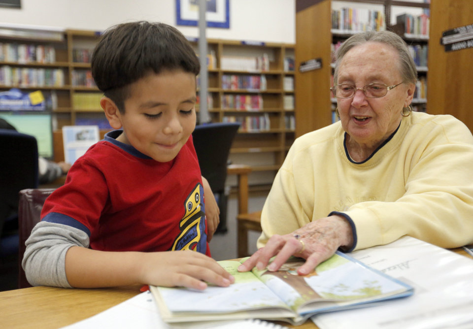 Photo - Alexander Lopez reads with Elmerta Haxton during a tutoring session at the Capitol Hill Library.  Photos by Sarah Phipps, The Oklahoman