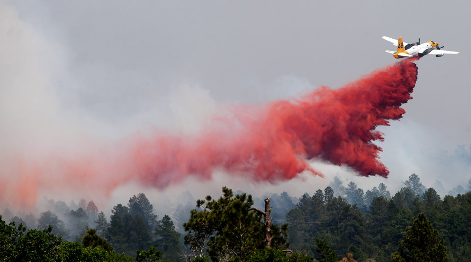 Photo - A slurry bomber makes a pass over the Black Forest fire north of Colorado Springs, Colo., Thursday, June 13, 2013. A voracious wildfire driven in all directions by shifting winds destroyed at least 360 homes — a number that was likely to climb as the most destructive blaze in Colorado history burned out of control for a third day through miles of tinder-dry woods. (AP Photo/The Colorado Springs Gazette, Michael Ciaglo)  MAGS OUT