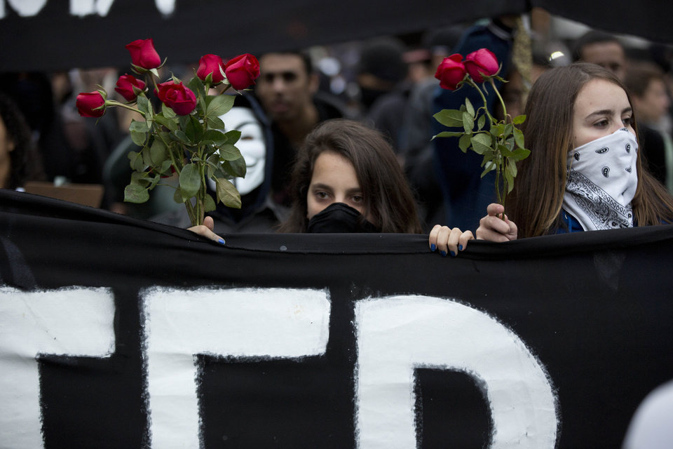 Photo - Masked protesters carry a banner and roses while marching in Sao Paulo, Brazil, Thursday, June 19, 2014. The protest in Sao Paulo, Brazil's biggest city that is hosting a World Cup match,  was called by the Free Fare movement, the group that was behind the first protests last year that sparked roiling anti-government demonstrations across Brazil. (AP Photo/Eduardo Verdugo)
