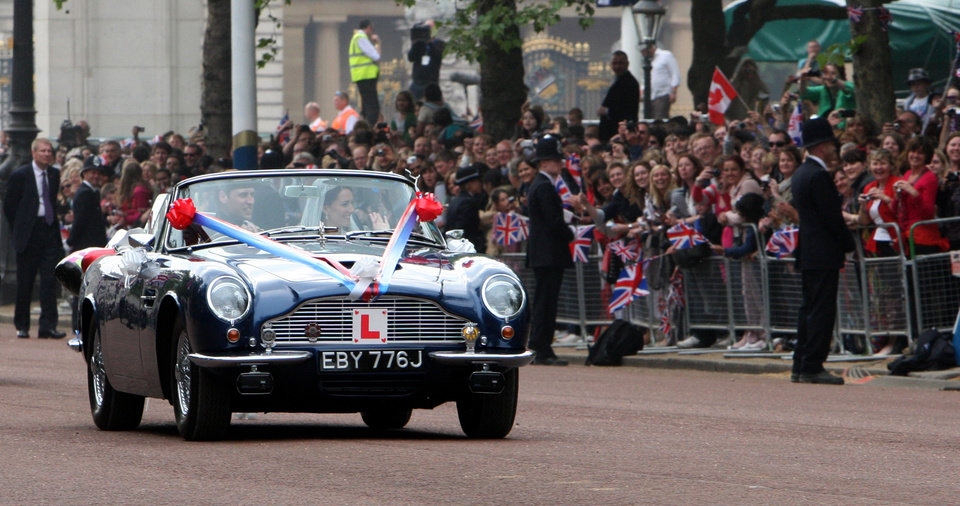 Photo - Britain's Prince William drives his wife, Kate, Duchess of Cambridge down the mall in London in his father Prince Charles' Aston Martin Volante sports car covered with bunting on their way to Clarence House after their wedding in nearby Westminster Abbey, in London Friday April 29, 2011. (AP Photo/Yui Mok, Pool) ORG XMIT: RWDJ146