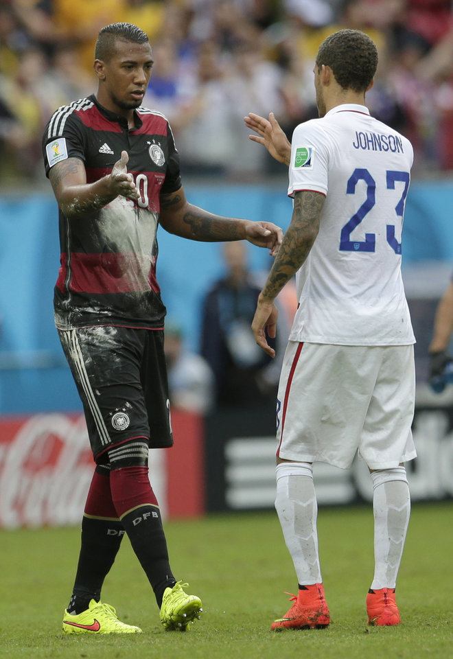 Photo - Germany's Jerome Boateng, left, and United States' Fabian Johnson shake hands after Germany won 1-0 during the group G World Cup soccer match between the USA and Germany at the Arena Pernambuco in Recife, Brazil, Thursday, June 26, 2014. (AP Photo/Petr David Josek)