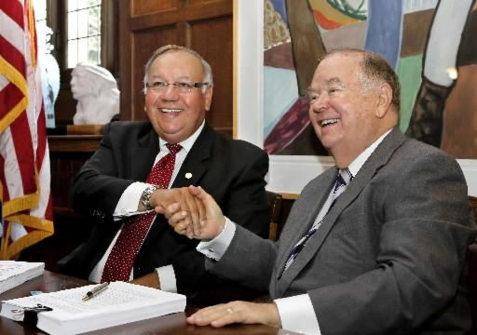 Photo - Chief George Tiger of the Muscogee (Creek) Nation, left, and David Boren, president of the University of Oklahoma, smile as they shake hands after signing documents in which the University of Oklahoma transferred ownership of the George Nigh Rehabilitation Center in Okmulgee to the Muscogee (Creek) Nation during a signing ceremony in Boren's office on Monday, Aug. 12, 2013. Photo by Jim Beckel