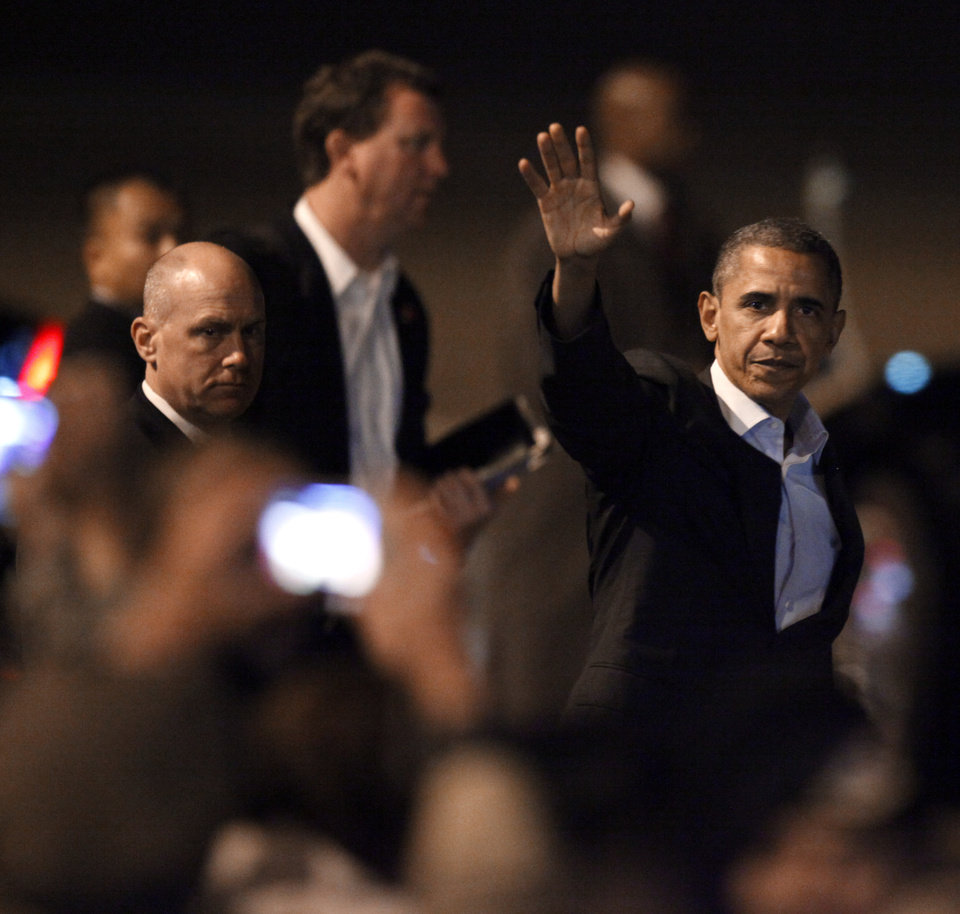 Photo - President Barack Obama waves to the crowd as he walks towards a car at Tinker Air Force Base in Midwest City, Wednesday, March 21, 2012. President Obama is in town for a visit to Cushing, Okla., on Thursday. Photo by Bryan Terry, The Oklahoman
