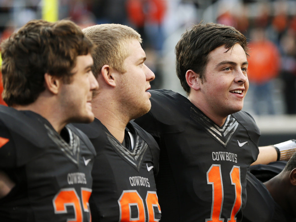 Photo - Oklahoma State's Wes Lunt (11), right, sings the alma mater along with Alex Elkins (37), left, and Zac Veatch (86) after a college football game between Oklahoma State University (OSU) and Texas Christian University (TCU) at Boone Pickens Stadium in Stillwater, Okla., Saturday, Oct. 27, 2012. OSU won, 36-14. Photo by Nate Billings, The Oklahoman