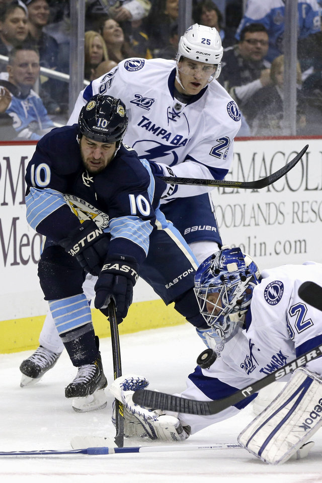 Photo - Pittsburgh Penguins center Tanner Glass (10) battles for a rebound with Tampa Bay Lightning goalie Anders Lindback (39) and Tampa Bay Lightning defenseman Matt Carle (25) in the second period of an NHL hockey game in Pittsburgh Sunday, Feb. 24, 2013. (AP Photo/Gene J. Puskar)