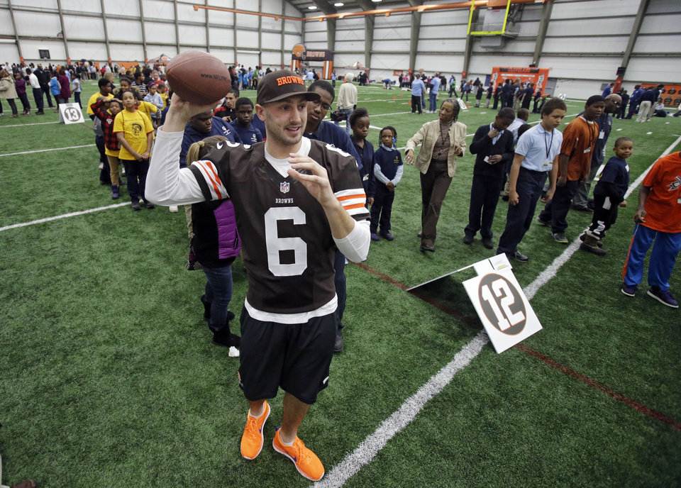 Photo - Cleveland Browns quarterback Brian Hoyer (6) throws to area Special Olympians at the NFL team's Play 60 football festival at their practice facility in Berea, Ohio Thursday, Feb. 13, 2014. (AP Photo/Mark Duncan)