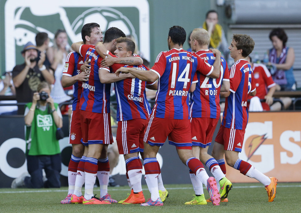 Photo - Bayern Munich players rush to congratulate Robert Lewandowski, second from left, after he scored a goal against the MLS All-Stars in the first half of the MLS All-Star soccer game, Wednesday, Aug. 6, 2014, in Portland, Ore. (AP Photo/Ted S. Warren)