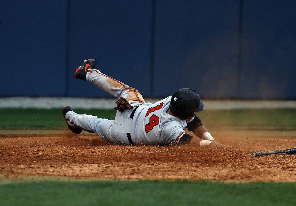 Photo - OSU's Robie Rojas slides into home plate uncontested during the OSU-ORU baseball game at J.L. Johnson Stadium, on Tuesday, April 22, 2014. CORY YOUNG/Tulsa World
