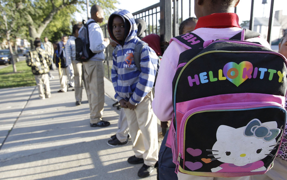 Photo -   Students gather outside Benjamin E. Mays Academy , Wednesday morning, Sept. 19, 2012 in Chicago, after Chicago teachers voted to suspend their first strike in 25 years. Union delegates voted overwhelmingly Tuesday night to suspend the walkout after discussing a proposed contract settlement with the nation's third largest school district. (AP Photo/M. Spencer Green)
