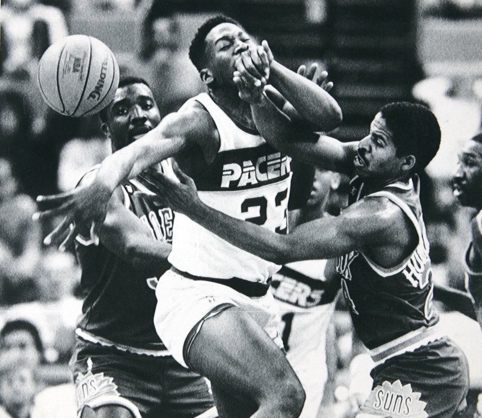 Photo - Former OU basketball player Wayman Tisdale. INDIANAPOLIS, Jan. 24 --ON THE CHIN --Indiana Pacer Wayman Tisdale (middle) is hit on the chin by Phoenix Suns guard Jay Humphries (right) as they scramble for a loose ball during NBA action in Indianapolis Sunday. Looking on is Armon Gilliam of the Suns (left). The Pacers defeated the Suns 128-109. (AP Laserphoto) (trs11620str-Tom Strattman) 1988. Opubco cutline - Indiana Pacer Wayman Tisdale, middle, gets hit on the chin while Phoenix Suns Jay Humphries, right, and Armon Gilliam scramble for the ball in Sunday's NBA game at Indianapolis. 1-25-88. ORG XMIT: KOD