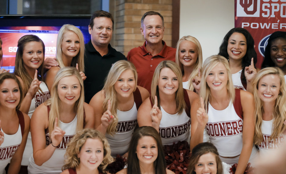 Photo - University of Oklahoma football coach Bob Stoops and men's basketball coach Lon Kruger pose for a photo with the OU cheer squad during the Sooner Caravan at the Jim Thorpe Museum in Oklahoma City, Okla. on Wednesday, July 30, 2014.  Photo by Chris Landsberger, The Oklahoman