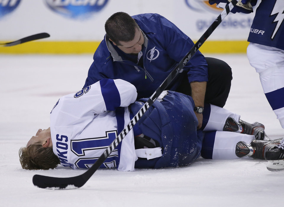 Photo - Tampa Bay Lightning center Steven Stamkos is attended to on the ice after banging into the goalpost during the second period of an NHL hockey game against the Boston Bruins in Boston Monday, Nov. 11, 2013. Stamkos was taken off the ice on a stretcher after the play. (AP Photo/Elise Amendola)