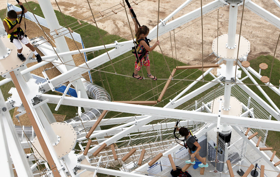 Photo - Adventure seekers go through  obstacle courses on the Sandridge Sky Trail along the Oklahoma River.  KT King - The Oklahoman