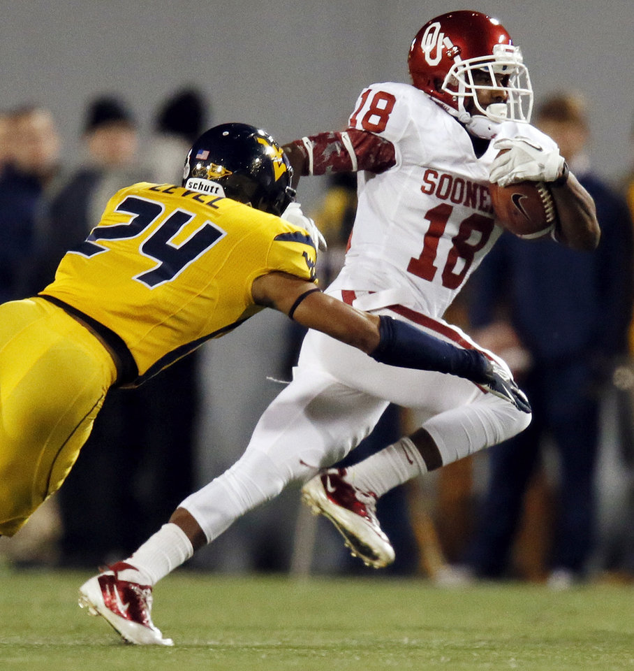 Photo - Oklahoma's Jalen Saunders (18) breaks away from West Virginia's Cecil Level (24) on a long run after a catch for a touchdown in the second quarter during a college football game between the University of Oklahoma (OU) and West Virginia University on Mountaineer Field at Milan Puskar Stadium in Morgantown, W. Va., Nov. 17, 2012. Photo by Nate Billings, The Oklahoman