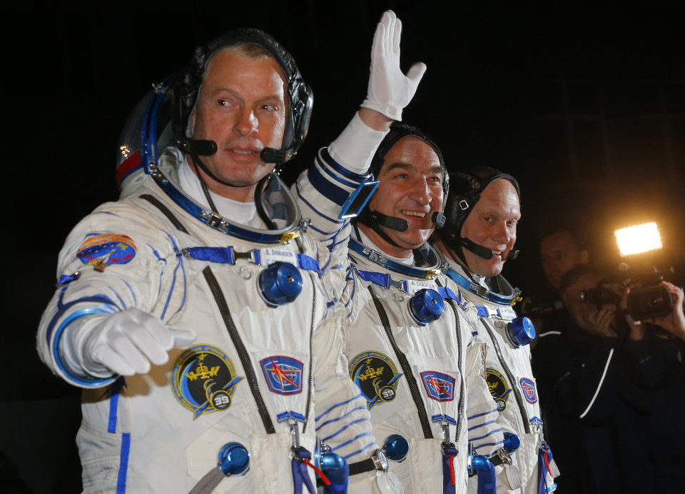 Photo - U.S. astronaut Steven Swanson, left, Russian cosmonauts Alexander Skvortsov, center, and Oleg Artemyev, crew members of the mission to the International Space Station (ISS) walk prior the launch of Soyuz-FG rocket at the Russian leased Baikonur cosmodrome, Kazakhstan, Wednesday, March 26, 2014. (AP Photo/Dmitry Lovetsky, Pool)