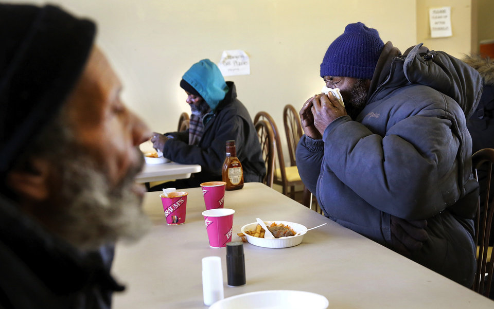 Photo - A man covers his face as he sneezes while eating with other homeless people in the dining hall at the Jesus House. Many in Oklahoma are dealing with frigid sub-freezing temperatures, part of a major winter storm that continues to grip much of the central sections and the eastern half of the United States. Photo taken Monday, Jan. 6, 2014.  Photo by Jim Beckel, The Oklahoman