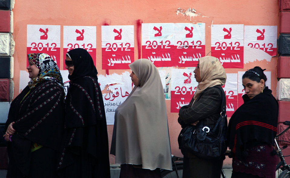 Photo - Egyptian women line up outside a polling station next to stickers on a wall with Arabic writing that reads