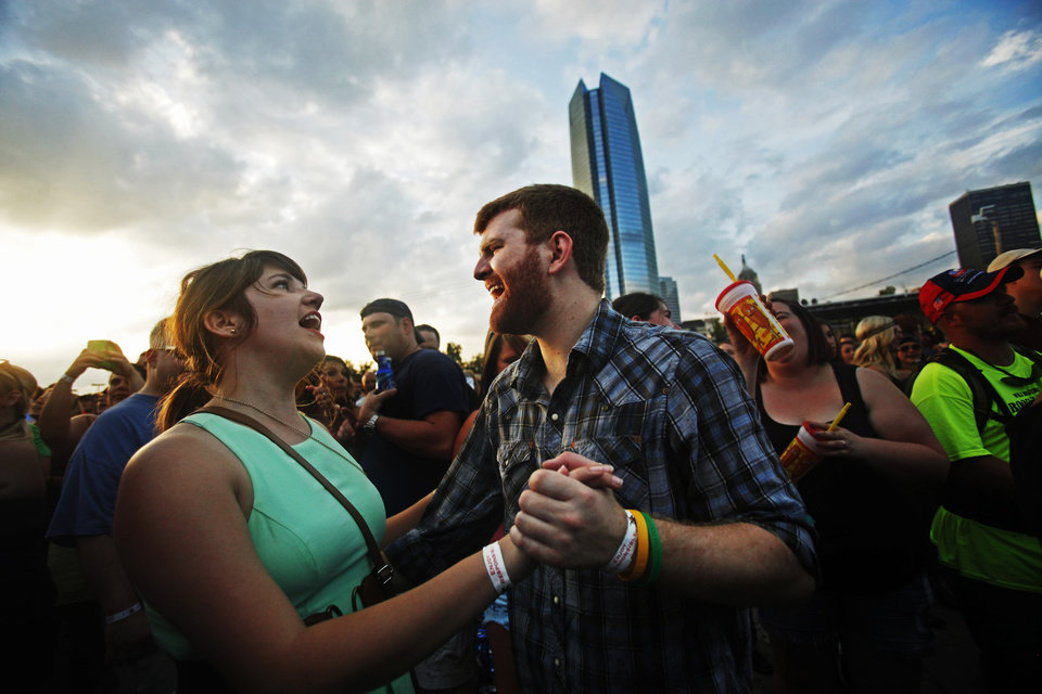 Photo -  Cayla Lewis and Michael Hendrick, of Oklahoma City, dance as the Josh Abbott Band performs at OKCFest in downtown Oklahoma City on Friday. OKCFest is a two-day country music festival with multiple stages downtown. Photos by KT King, The Oklahoman