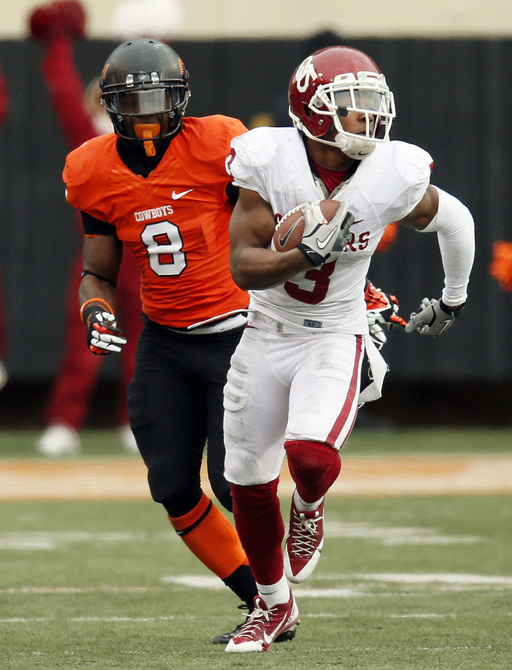 Photo - Oklahoma's Sterling Shepard (3) runs after a catch in front of Oklahoma State's Daytawion Lowe (8) in the fourth quarter during the Bedlam college football game between the Oklahoma State University Cowboys (OSU) and the University of Oklahoma Sooners (OU) at Boone Pickens Stadium in Stillwater, Okla., Saturday, Dec. 7, 2013. OU won, 33-24. Photo by Nate Billings, The Oklahoman